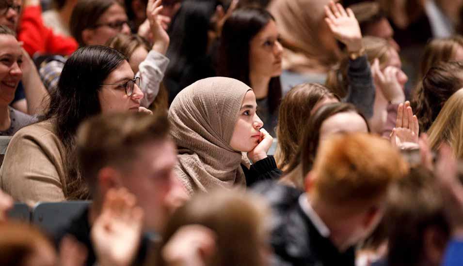 mehrere Studierende in einem vollen Hörsaal heben die Hand zur Wortmeldung