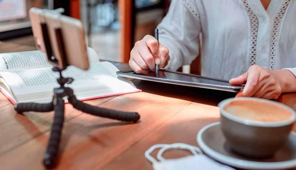 Frau sitzt am heimischen Arbeitsplatz mit Tablet und Smartphone auf einem Stativ - mauritius images / Theera Disayarat / Alamy